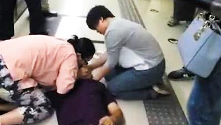 地铁站乘客突然晕倒 妙龄女跪地人工呼吸