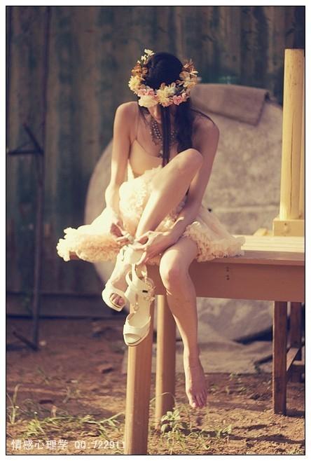 一外国美女翘着二郎腿穿着白色的类似婚纱坐在凳子