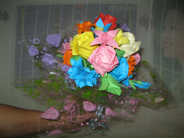 剪刀,胶水,还有包花的塑料彩纸,我用了20个小时折了11朵,做成一束的图片